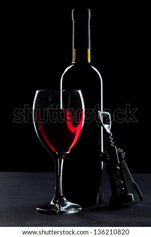 Wine glass and bottle on black background still life - stock photo