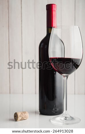 Wine glass and bottle on white table - stock photo