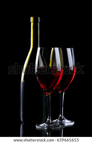 Wine glass and bottle with red wine isolated on black background