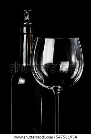 Wine glass and bottle with stopper on black background in vertical format