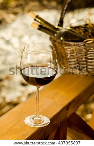 Wine glass and bottles in picnic basket with straw near water in twilight. Vintage look