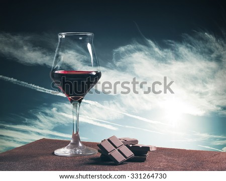 Wine glass and chocolate with blue cloudscape - stock photo