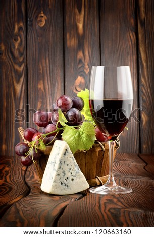 Wine glass and grapes in a basket on a wooden background - stock photo
