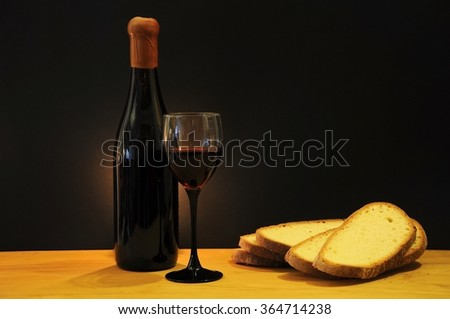 Wine glass and old bottle on a wooden table with slices of Tuscan bread - stock photo