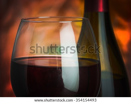 Wine, glass and the bottle on a colored background