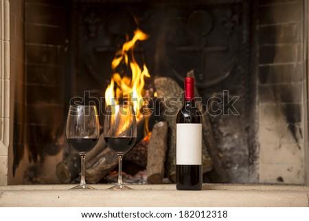 Wine glass and wine beside fireplace. - stock photo