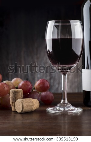 Wine glass , Bottle and Grapes on a wooden background