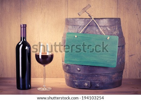 Wine glass, bottle, old wood barrel and sign board - stock photo