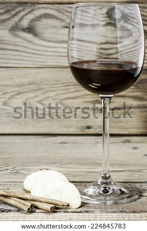 Wine glass, cinnamon sticks and slices of apple on a wooden background