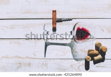 Wine glass, cork and corkscrew over wooden table - stock photo