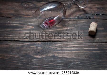Wine glass, cork and corkscrew over wooden table with copy space. - stock photo