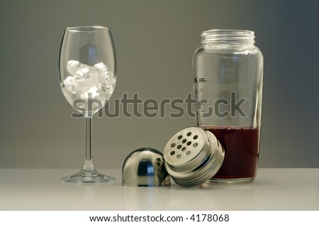 Wine glass filled with ice and an open mixer with red cocktail - stock photo
