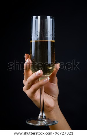Wine glass in a hand of the girl on a black background