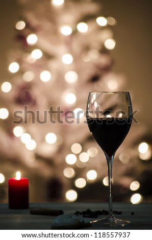 Wine glass on a table decorated with candle and cookies. De-focused lights on a white Christmas tree in background.