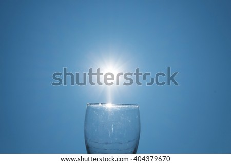 Wine glass on blue sky with sun lens flare effects - stock photo