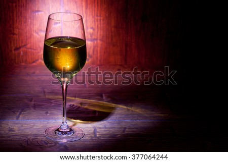 Wine glass on red old wooden background. With place for text. - stock photo