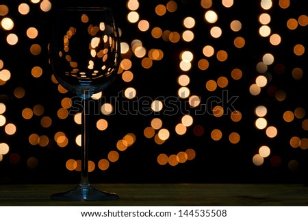 Wine glass on wooden table with dark and bokeh background distant lights - stock photo