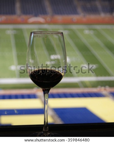 Wine glass or crystal goblet with red wine overlooking empty football field  - stock photo