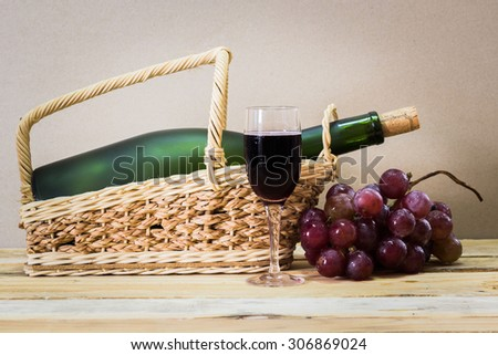 Wine Glass with bottle of red wine and cluster of grape on wooden table - stock photo