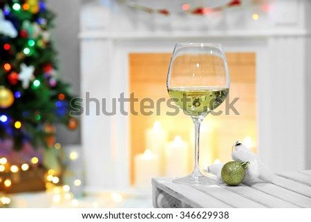Wine glass with Christmas decor on fireplace background - stock photo