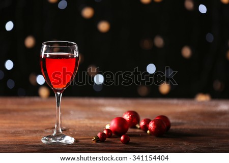 Wine glass with Christmas decorations on wooden table - stock photo