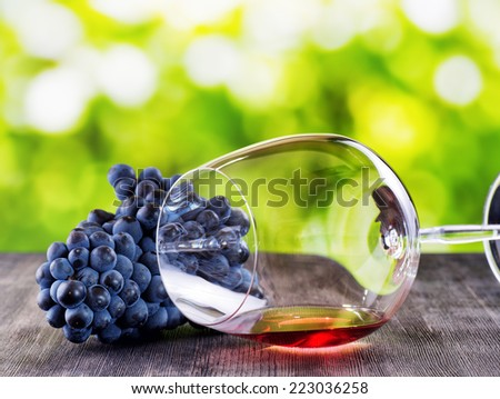 Wine glass with grape on wooden table. - stock photo