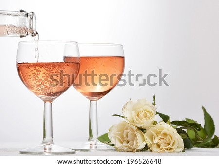 wine glass with red sparkling drink poured in and white roses - stock photo