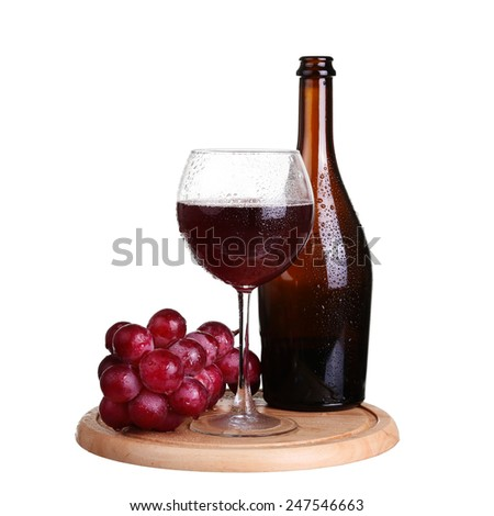 wine glass with red wine, bottle of wine and grapes on board isolated over white background