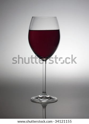 Wine glass with red wine in back light. - stock photo