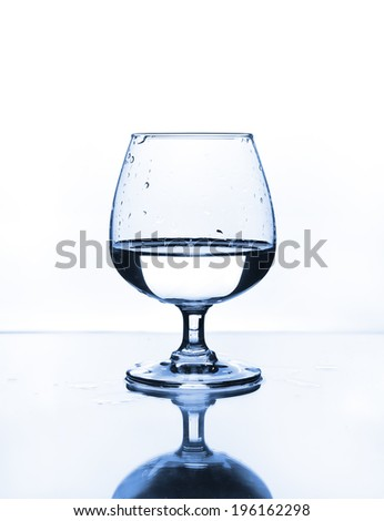 wine glass with water on glass table - stock photo