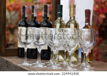 Wine glasses and a bottle on a table - stock photo