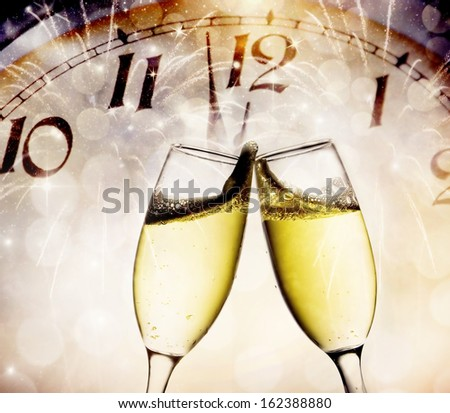 Wine glasses and clock at midnight - stock photo