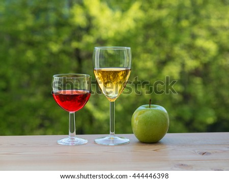 wine glasses and green apple on table in the garden - stock photo