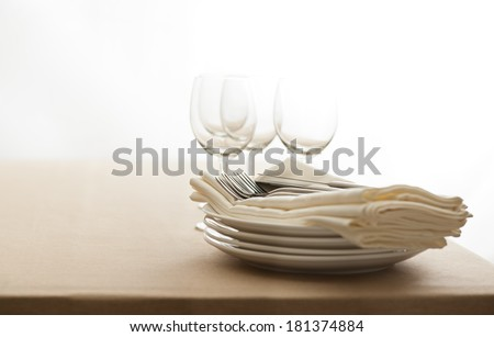 Wine glasses, cutlery, plates and napkins on a table - stock photo