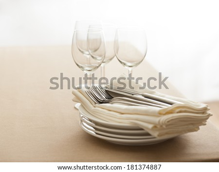 Wine glasses, cutlery, plates and napkins on a table