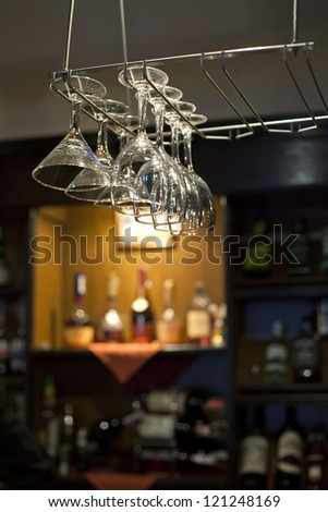Wine glasses hanging near bar counter with wine bottles on the background