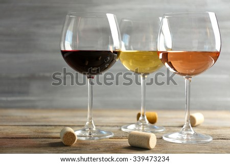 Wine glasses in a row and corks on wooden table against grey background - stock photo