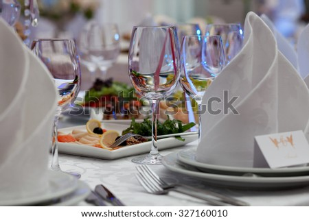 Wine glasses, napkins and salad on the table for the banquet. - stock photo