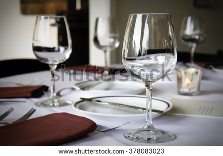 Wine glasses on a formal table setting at a fund raising event. Also on the table are some red napkins, a plate, silverware and a small votive candle.