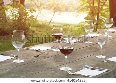 wine glasses on a wooden table outdoor in the countryside