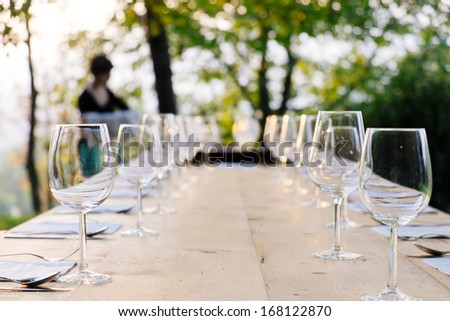 wine glasses on settled table outdoor - stock photo