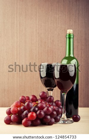 wine glasses on table and bottle with grapes