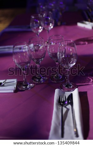Wine glasses set on a dinner table at a wedding.