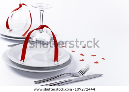 Wine glasses turned upside down with red decoration as background for invitation and menu - stock photo