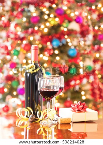Wine glasses, vintage cork screw, present, and unopen wine bottle on Mahoney table with bright Christmas tree lights in background.  Vertical format layout.