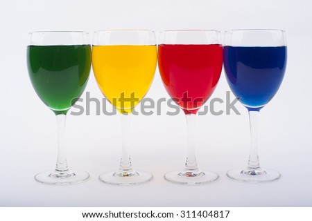 Wine Glasses with Brightly Colored Water on a White Background - Red, Blue, Yellow, Green