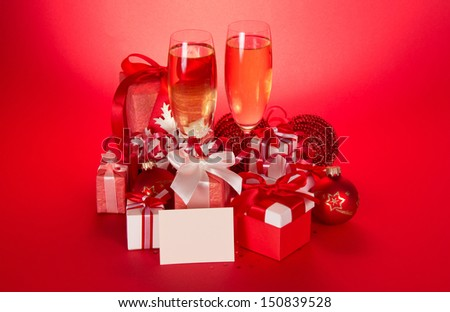 Wine glasses with champagne, gift boxes, Christmas spheres, snowflake and blank card on a red background