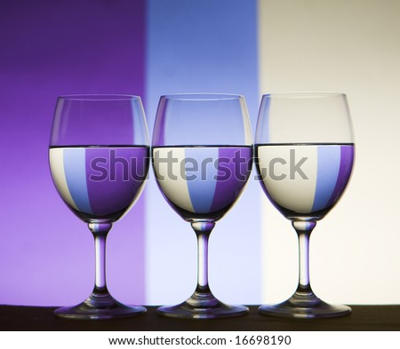 wine glasses with colored background refracted - stock photo