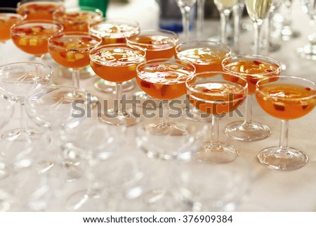 Wine glasses with red apple punch on the table - stock photo