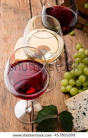 Wine glasses with red, white and rose. Cheese on wooden table with fresh grapes  - stock photo